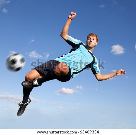 Male football player kicking the ball in the air