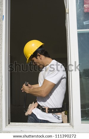 Male foreman working nearby window at construction site - stock photo