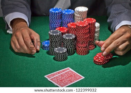 Male gambler playing in the casino on the green table - stock photo