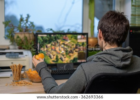 male gamer playing strategy game on computer with snacks lying on table - stock photo