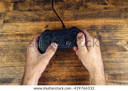 Male gamer using gamepad controller on wooden desk, flat lay top view, gaming and entertainment concept - stock photo