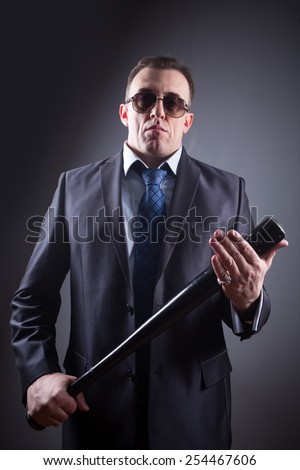 male gangster with glasses and a baseball bat - stock photo