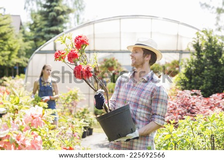 Male gardener examining flower pot with colleague standing in background outside greenhouse - stock photo