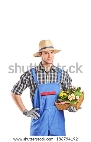 Male gardener holding a basket with flowers isolated on white background