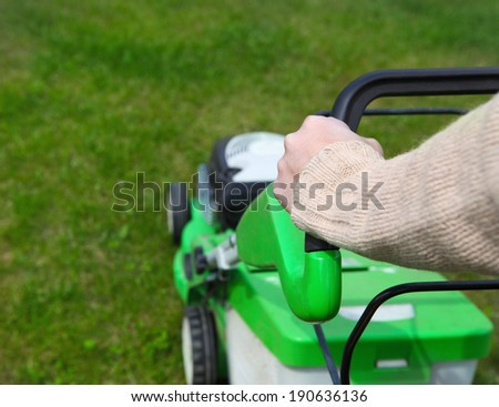 Male gardener mowing the lawn. Gathering - stock photo