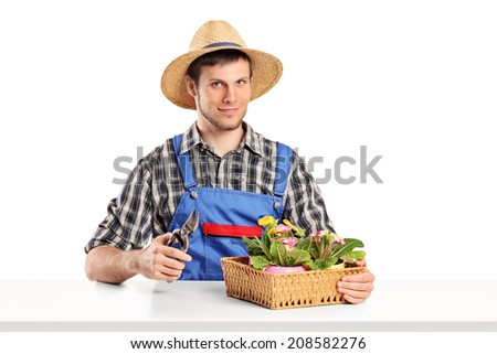 Male gardener sitting at a table with plants isolated on white background