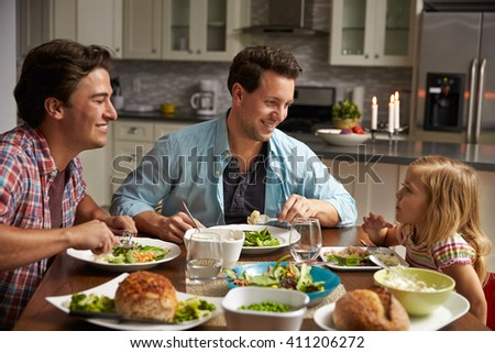 Male gay couple and daughter dining in their kitchen - stock photo