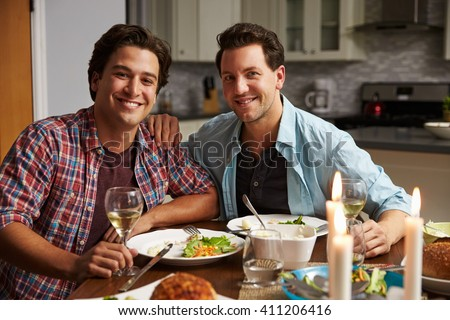 Male gay couple at home for a romantic dinner look to camera - stock photo