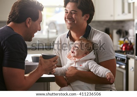 Male gay couple holding baby girl in their kitchen - stock photo