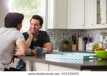 Male gay couple in their 20s talking in their kitchen - stock photo