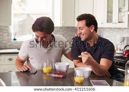 Male gay couple looking at smartphone over breakfast - stock photo