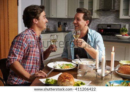 Male gay couple making a toast at dinner in their kitchen - stock photo