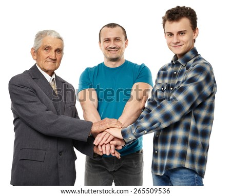 Male generations - grandfather, son and grandson holding hands, giving help and support each other - stock photo