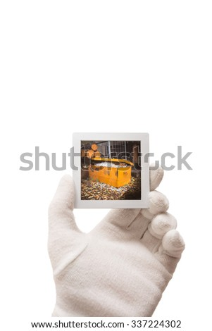 Male gloved hand holding a framed piece of slide film isolated on white