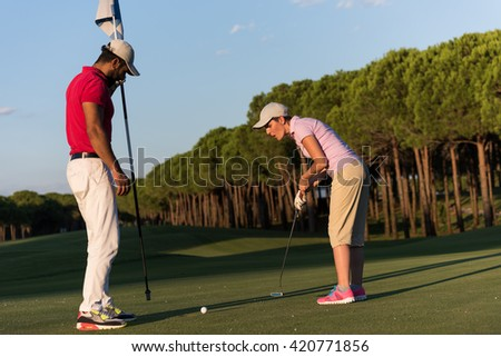 male golf instructor teaching female golf player, personal trainer giving lesson on golf course - stock photo