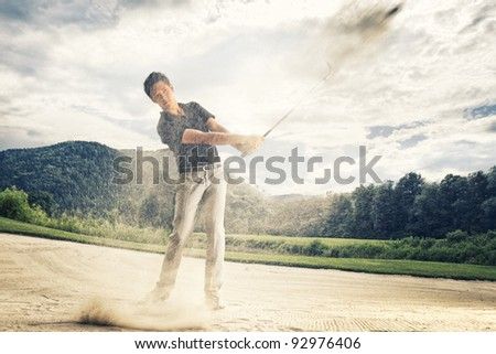Male golf player in blue shirt and grey pants hitting golf ball out of a sand trap with sand wedge and sand caught in motion. - stock photo