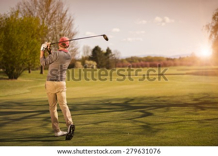 Male golf player swinging golf club for tee shot at beautiful sunset. - stock photo