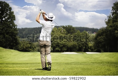 Male golf player teeing-off golf ball at beautiful golf course with forest. - stock photo