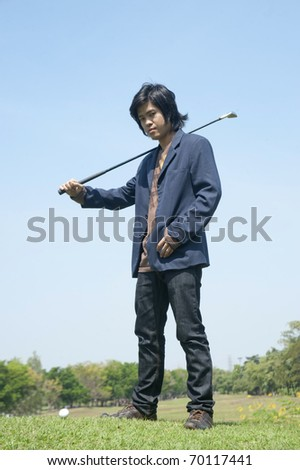 Male golf player teeing off golf ball from tee box - stock photo