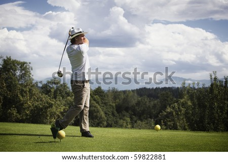 Male golf player teeing off golf ball from tee box, wonderful cloud formation in background. - stock photo