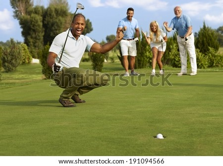 Male golfer and partners happy for successful putt on the green.