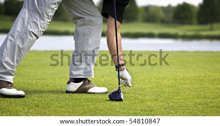 Male golfer arranging tee with ball to tee off. - stock photo