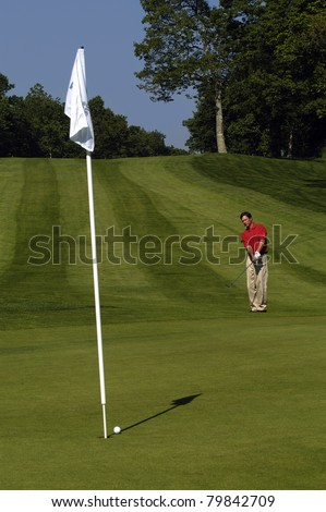 Male golfer looking at ball after putting. - stock photo