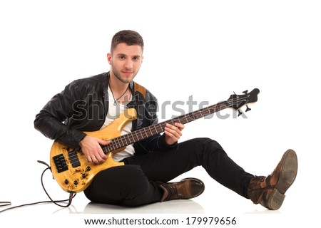 Male guitarist sitting on a floor and play the bass guitar. Full length studio shot isolated on white.
