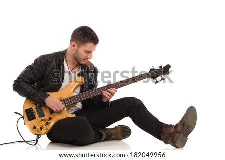 Male guitarist sitting on a floor and plays the bass guitar. Full length studio shot isolated on white.
