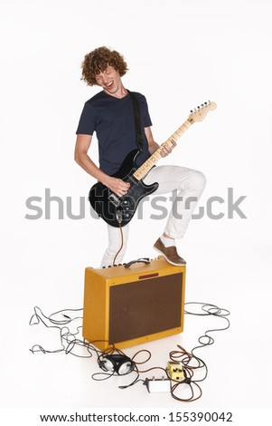 Male guitarist standing with one leg on a guitar amplifier and playing his guitar passionately, isolated on white - stock photo