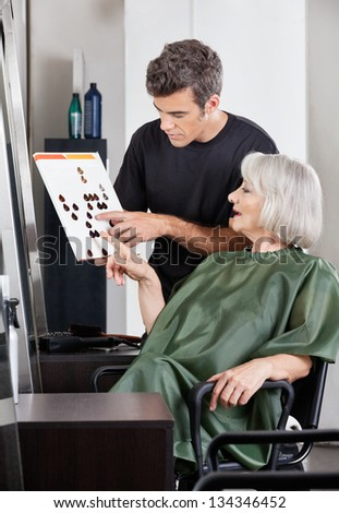 Male hairdresser advising female client in selecting hair color from catalogue
