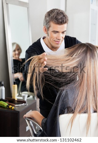 Male hairdresser attending customer with senior client in background in hair salon