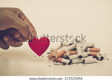 male hand choosing to pick up a red heart next to destroyed cigarettes - stop smoking - making a decision to have a healthy life by stop smoking - stock photo