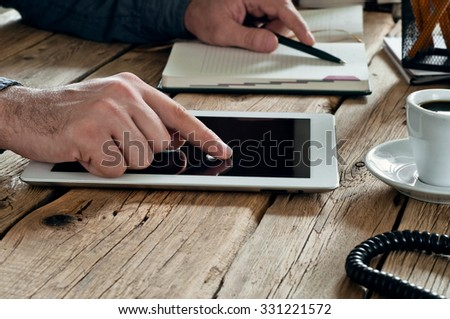 male hand clicks on a blank screen tablet computer closeup. Man working in office using tablet computer. Copy space. Free space for text - stock photo