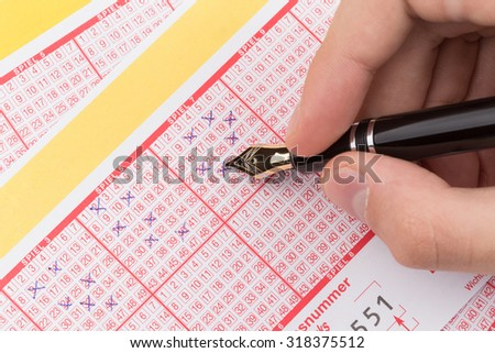 male hand filling fountain pen lotto ticket - stock photo
