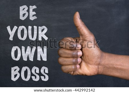 Male hand giving the thumbs up gesture to the phrase Be Your Own Boss written on a blackboard - stock photo