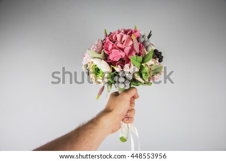 male hand giving wedding bouquet, first-person view - stock photo
