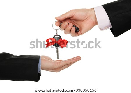 male hand handing over the key of a new car - stock photo