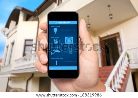 male hand hold a phone with system smart house on a screen on the background of the house - stock photo