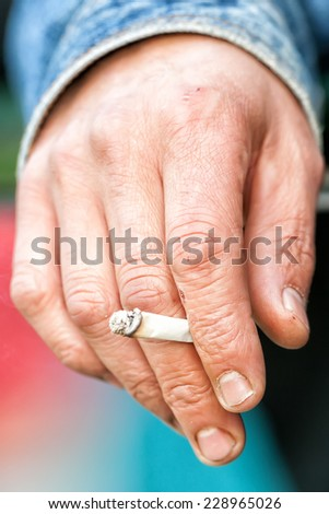 Male hand holding a cigarette.  - stock photo