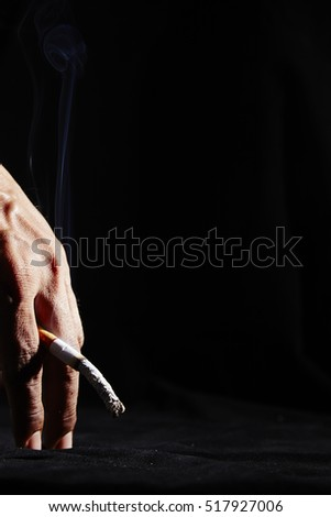 Male hand holding a cigarette, Isolated on black background, Concept cigarettes causes sexual dysfunction.