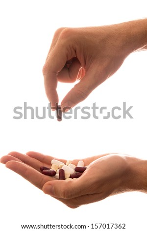 Male hand holding a handful of medical pills and picking one isolated on white background - stock photo