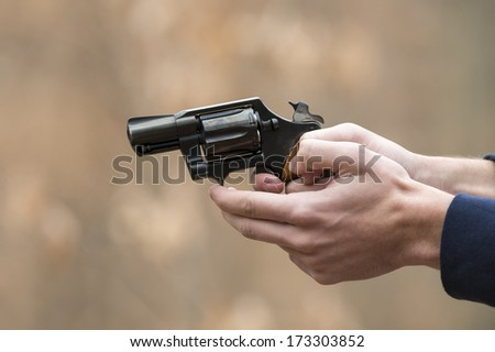 Male hand holding a pistol with a shallow depth of field