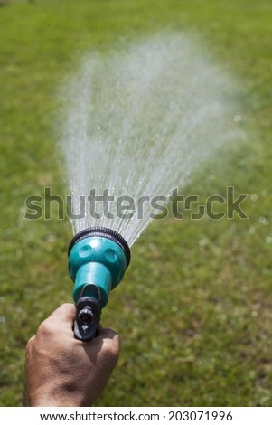 male hand holding a shower that sprayed water on the lawn - stock photo