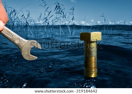 Male hand holding a wrench in front of a bolt coming out of the blue selective color lake water on a sunny Autumn afternoon in Finland with ecology, environmental protection and green concept idea.  - stock photo