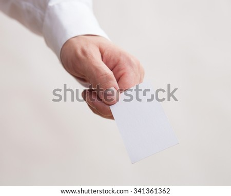 Male hand holding an empty business card,  neutral background - stock photo
