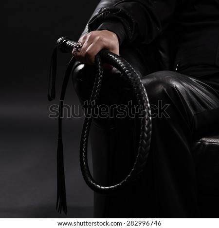 male hand holding black leather whip - stock photo