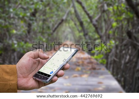 Male hand holding black mobile smartphone with map gps navigation application with planned route on the screen. Abstract pastel blurred background - stock photo