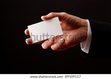 Male hand holding blank business card. Add your own design - stock photo