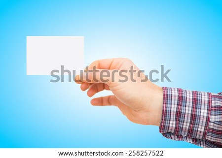 Male hand holding blank card - blue gradient background